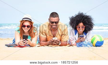 Row of multicultural friends using phone lying on beach - Happy african and american students on summer vacation texting messages are looking addicted at mobile technology and social media post -