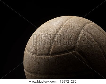Old used vintage volleyball on a dark background