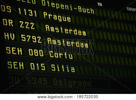 Flight information board at airport terminal closeup.