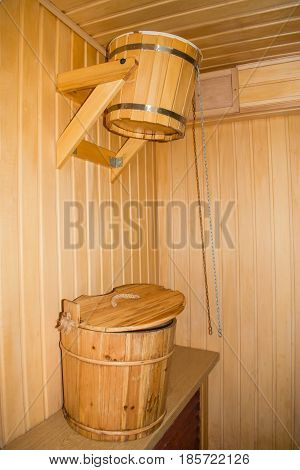 Wooden bucket for pouring cold water and a bucket with a lid in the bath the steam room