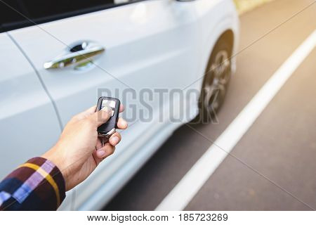 Men on hipster shirt hand presses on the remote control car systems with sunlight along site the road