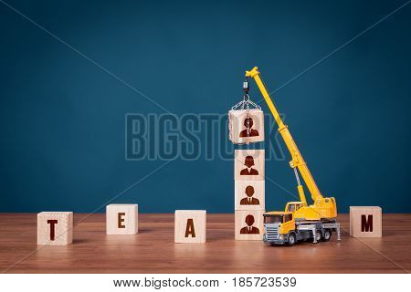 Build team hire and recruitment concepts. Recruiter represented by crane complete team.