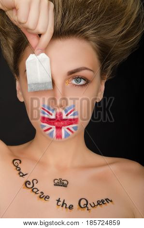 Woman with english flag on face and tea bag black background