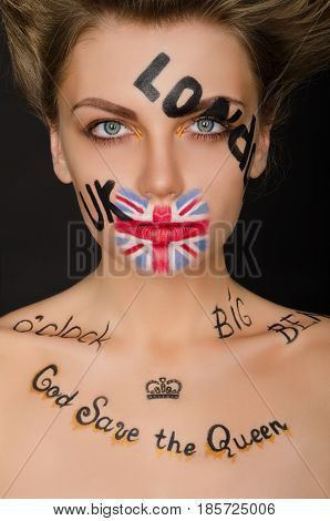 Beautiful woman with english symbols on her face black background