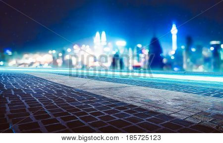 Empty marble floor with blue neon lights circulating underneath the stone with abstract blur bokeh city background .
