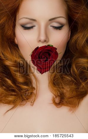 Red rose in the teeth of woman with long hair