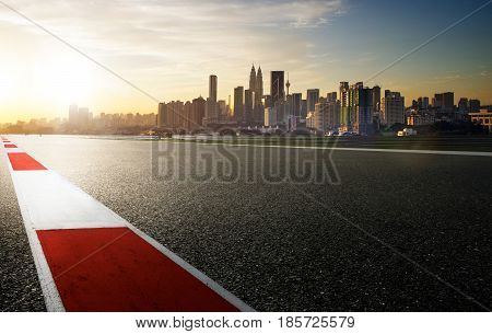 Racetrack with red and white safety sideline modern city background sunrise scene .