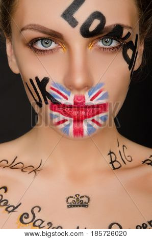 Inscriptions and flag of england on woman's face black background