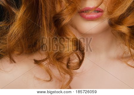 Beautiful curly long red hair on the face of young woman