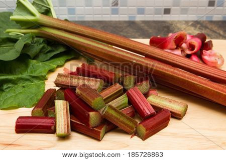Rhubarb Freshly prepared stalks of rhubarb on a wooden chopping board