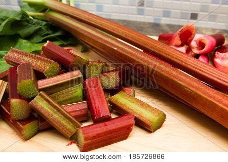 Rhubarb Freshly prepared stalks of rhubarb on a wooden chopping board