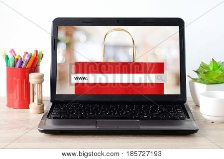 Lap-top computer with www. on search bar over blur store on screen background online shopping concept business and technology template