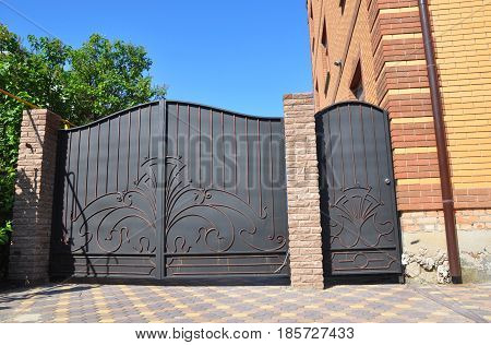 Installation of Stone and Metal Fence with Door and Gate for Car. Security CCTV camera is mounted on a brick house wall.