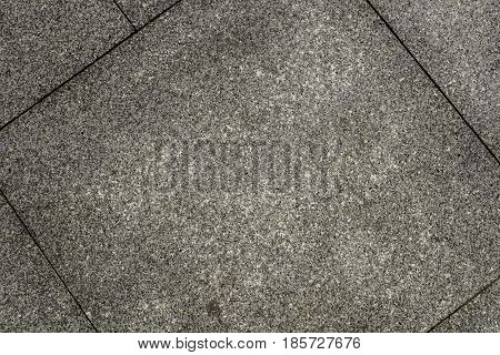 Old outdoor floor tiles with a coarse marble. Texture with prominent edges of the tiles diagonally.