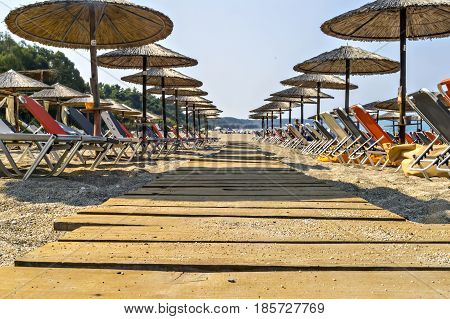 Wooden pathway on beautiful Ionian sandy resort beach in Greece with sunbeds and straw sunshades, umbrellas. Vacation destination. Public beach