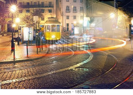 Famous vintage yellow 28 tram of of Alfama, in the oldest district of the Old Town, at night, Lisbon, Portugal