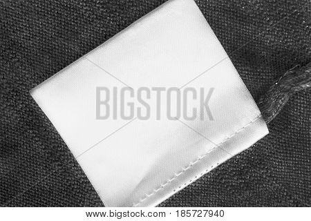 White blank clothes label on black knitted background closeup