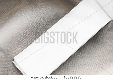 Blank white clothes label on beige cotton as a background closeup