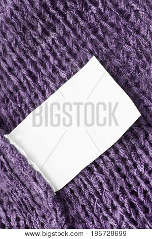 Blank white clothes label on purple knitted background closeup