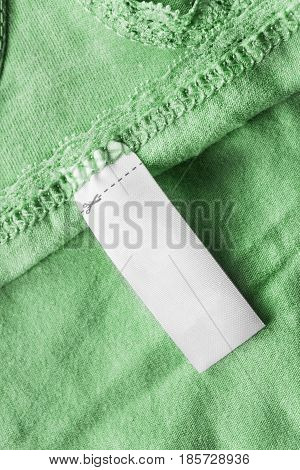 White blank clothes label on green cloth as a background