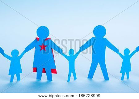 Super mom superhero. The best mom in the world. Paper family are holding hands and Mom has a superhero costume