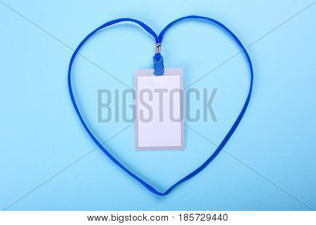 lanyard and badge blank space for text with blue ribbon in the shape of a heart. Blue or blue background