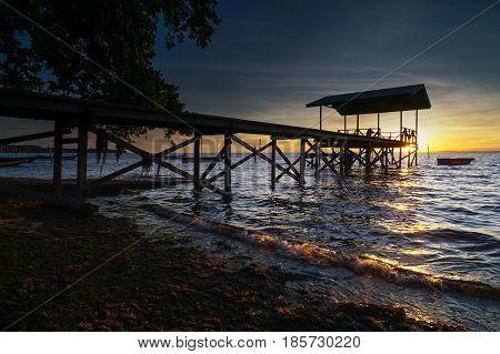 Serene sunrise beach over fishing jetty with fishing boats in Tanjung Aru village,Labuan island,Malaysia.