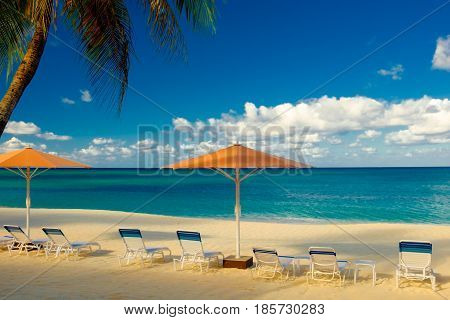 Parasols and Sun loungers on Seven Mile beach by the Caribbean Sea, Grand Cayman