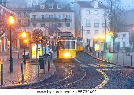 Famous vintage yellow 28 tram on street of Alfama, the oldest district of the Old Town, in the foggy morning, Lisbon, Portugal
