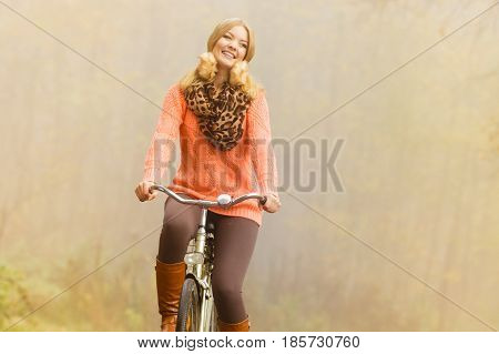 Happy active woman riding bike bicycle in foggy fall autumn park. Glad young girl in sweater and earmuffs relaxing. Healthy lifestyle and recreation leisure activity.
