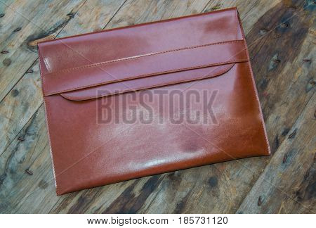 Brown leather business bag on wooden floor