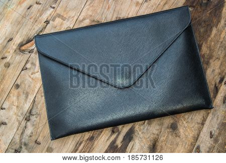 Black leather business bag placed on a wooden floor.