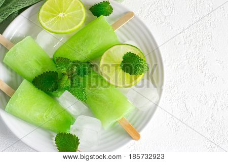 Healthy lime mint popsicles with fresh lime slices And ice cubes. Top view with copy space