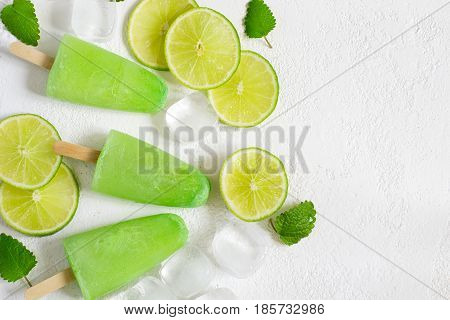 Refreshing background with Healthy lime mint popsicles with fresh lime slices And ice cubes. Top view