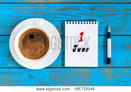 June 1st. Day of the month 1 , everyday calendar with morning coffee cup at blue wooden background. Summer concept, Top view.