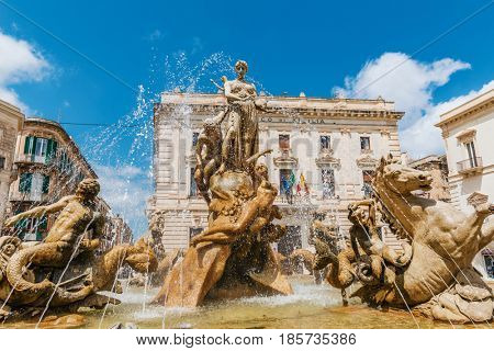SYRAKUSE, SICILY, ITALY - April 26, 2017: Famous Artemis (Diana) Fountain on Archimedes Square on the Ortygia isle - old town of Syracuse on Sicily island, Italy