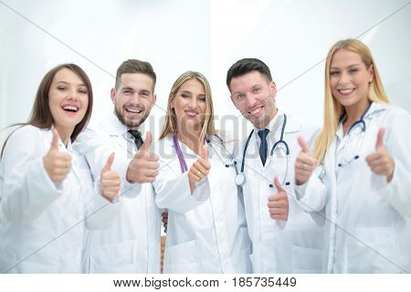Smiling team of doctors at hospital making selfie and showing th