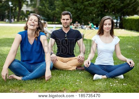 Happy friends practicing yoga in the park, sitting on the grass.