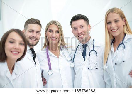Smiling team of doctors at hospital making selfie.