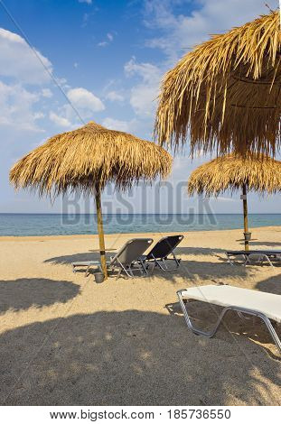 Beautiful Ionian sandy beach in Greece with with sunbeds and straw sunshades, umbrellas. Vacation destination