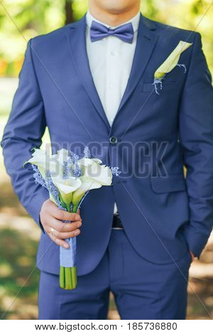 the groom in a beautiful blue suit with a bouquet of white Calla lilies in hand