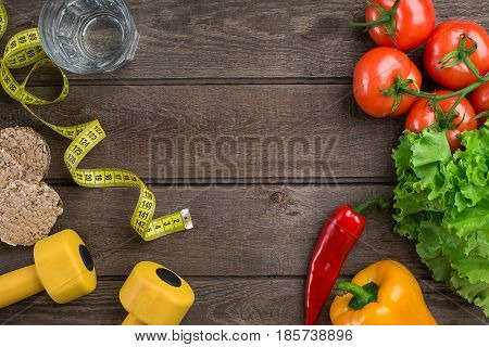 Sport and diet. Vegetables, dumbbells and centimeter. Peppers, tomatoes, salad on rustic background. Top view. Copy space