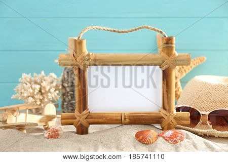 Travel concept. Bamboo frame with space for text and cute decorations on sand against color background