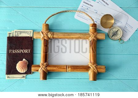 Travel concept. Bamboo frame with space for text, passport and tickets on wooden background