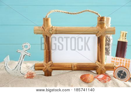Travel concept. Bamboo frame with space for text and travel accessories on sand against color background