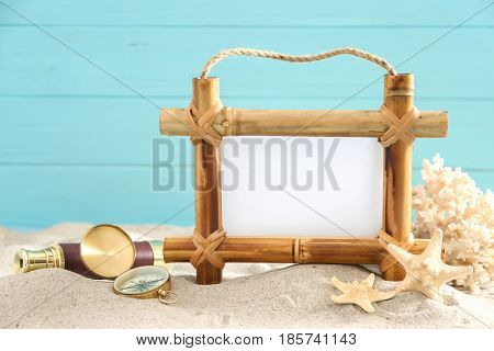 Bamboo frame with space for text and travel accessories on sand against color background