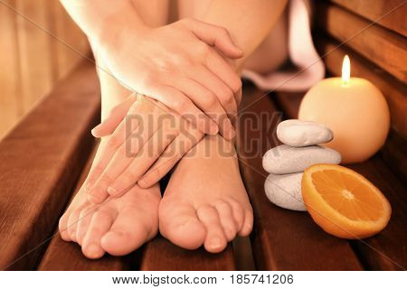 Young woman legs in sauna on wooden background