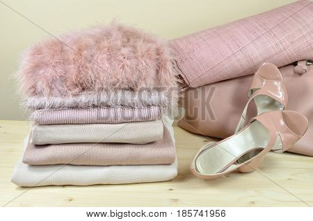 Pile of pink garments with pink sandals and bags beside it - on wooden shelf