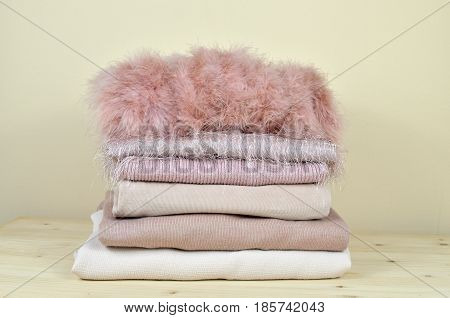 Pile of pink garments of different materials - feather cotton woolen corduroy velvet - on wooden shelf