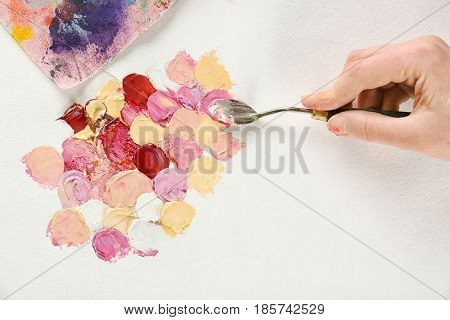 Woman using palette knife in oil painting